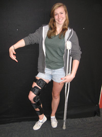 Colorado-Caldwell shows off her knee brace and crutches