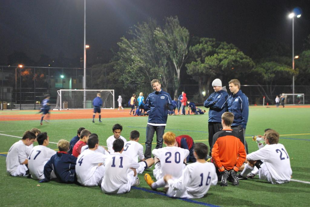 Head coach Antony Reyes speaks to his team in a huddle.
