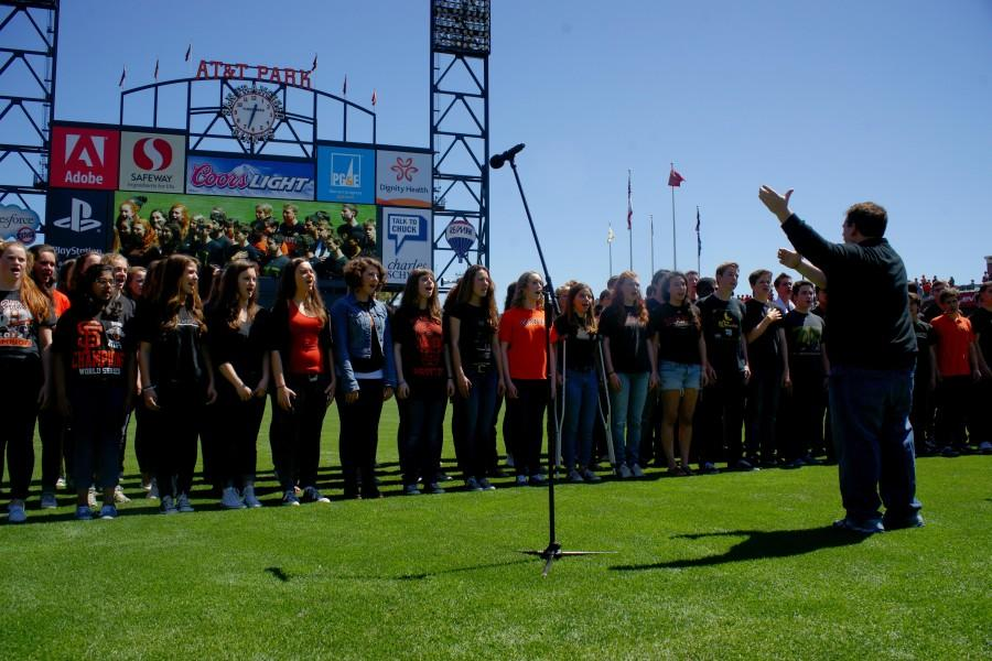 Urban Choral Director Brandon Adams leads the Urban Singers and students from Lick-Wilmerding High Schools chorus in the national anthem prior to the April 10 Giants vs. Rockies game at AT&T Park in San Francisco.
