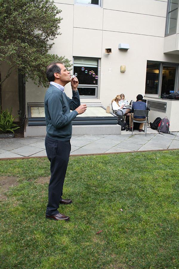 Mark Salkind, Head of School, blows bubbles in the garden.