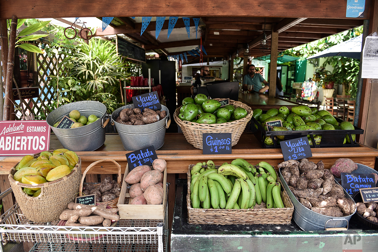This Sept. 23, 2016 photo shows a produce stand inside El Departamento de la Comida farmers market and organic restaurant that sells locally grown produce in San Juan, Puerto Rico. The most recent statistics from the governor's office show farm income grew 25 percent to more than $900 million from 2012-2014 while the amount of acreage under cultivation rose 50 percent over the past four years, generating at least 7,000 jobs. (AP Photo/Carlos Giusti)